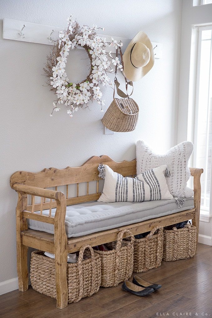 Simple spring touches in the entryway are a sweet greeting to family and friends. Easy accents such as a wreath, pillows, vintage tackle basket, and floppy hat are so charming through Spring and Summer.
