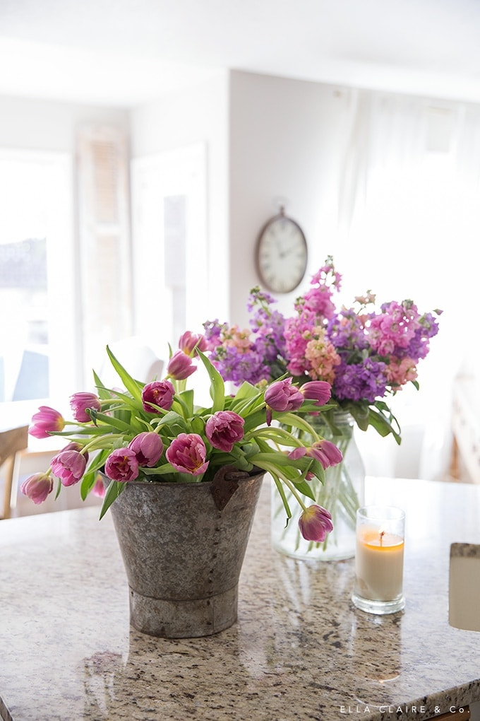 Tulips and stock flower arrangement in a vintage bucket make the perfect Spring centerpiece for Easter entertaining.