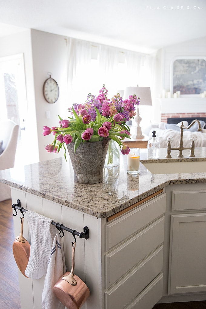 Copper is a lively accent paired with spring colored tulips and stock in a rustic vintage bucket- the perfect Easter accents to a white kitchen.