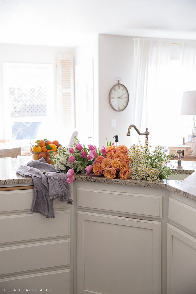 A french country inspired home with a bright and cheerful spring flower arrangement- with an easy DIY centerpiece from grocery store flowers in colors of pink, orange, and yellow.