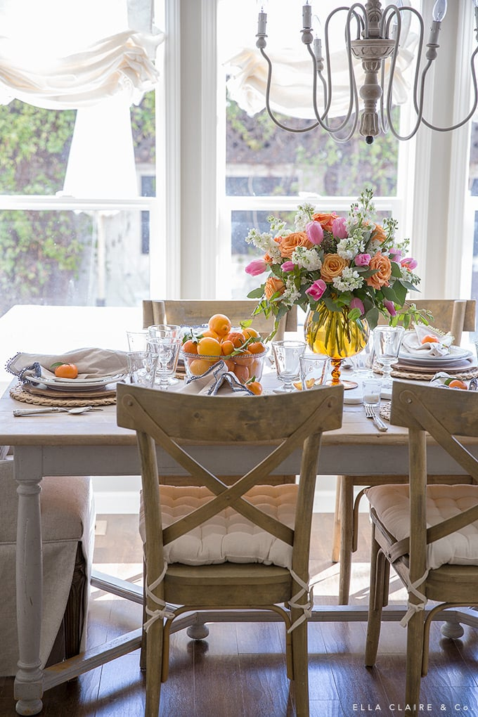 A french country inspired dining room with a bright and cheerful spring tablescape- with an easy DIY centerpiece from grocery store flowers in colors of pink, orange, and yellow.