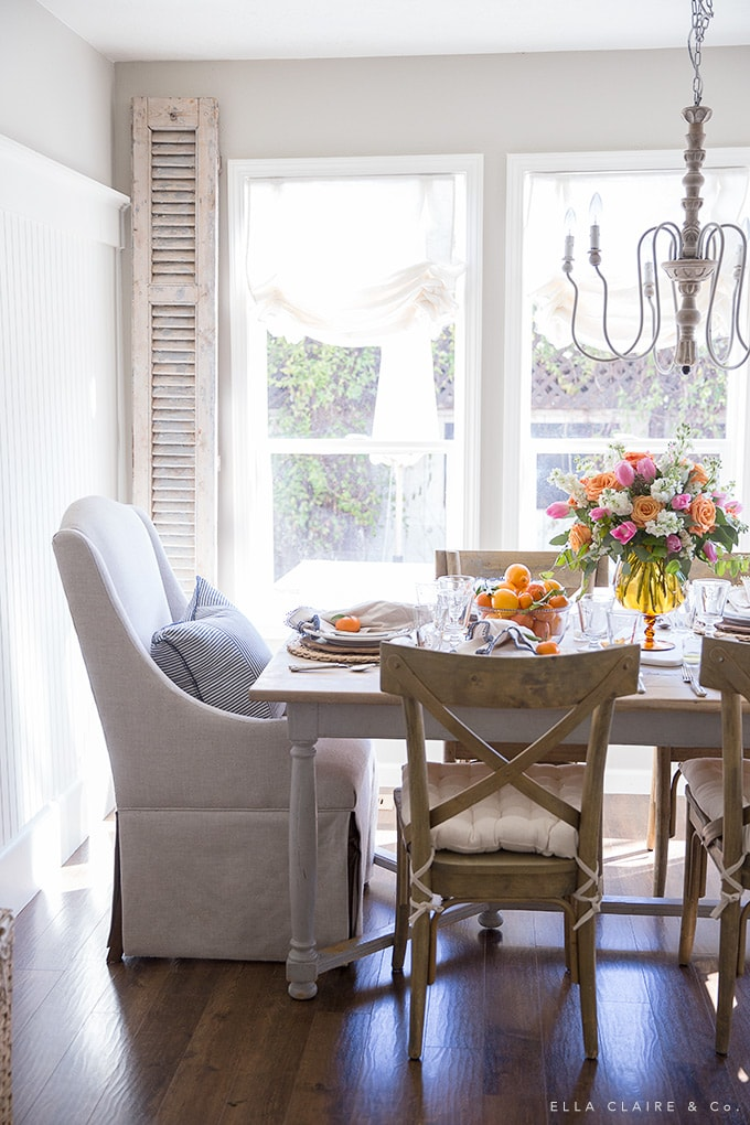 Create a spring tablescape with thrifted vintage finds and bright, colorful flowers and fruits.