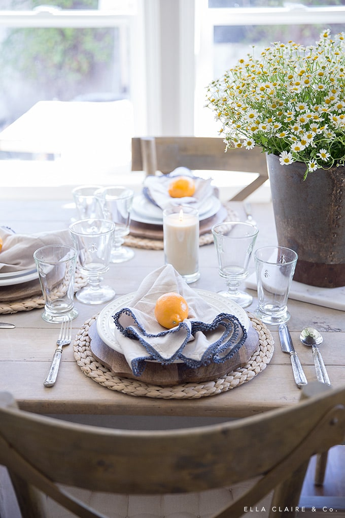 Keeping key pieces of neutral dishes, glasses, and flatware on hand makes a quick and easy table. This French Farmhouse inspired table is decorated with lemons, chamomile, and vintage accents.
