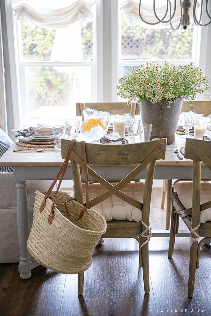 Lemons, a bucket of chamomile, and a french market basket make a casual and inviting tablescape for spring or summer.