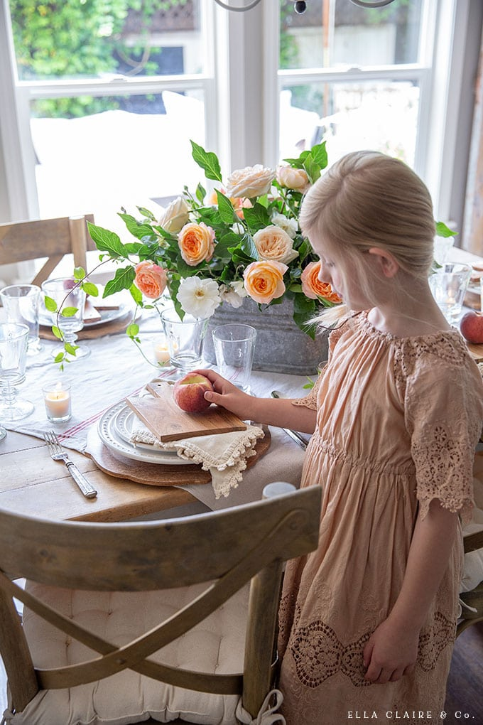 A summer tablescape with fresh peaches and garden roses. Use mini breadboards at each place setting along with cloth napkins and wood chargers to add a layered vintage feel.