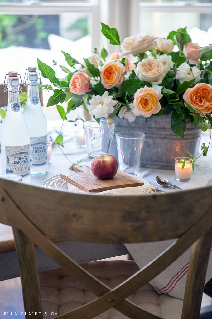 Fresh peaches at each place setting make this summer tablescape feel special paired with this simple DIY garden rose flower arrangement.
