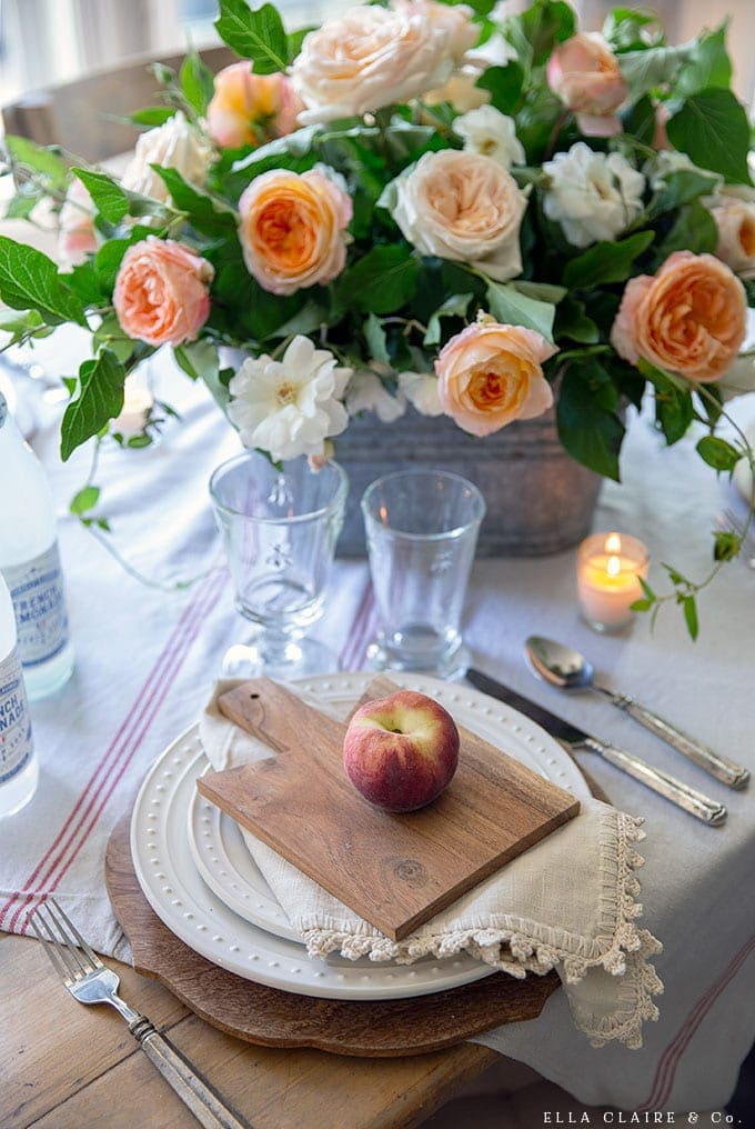 Create this sweet summer tablescape where each place setting has a mini breadboard and a fresh peach. Inexpensive touches for vintage French farmhouse inspired entertaining.