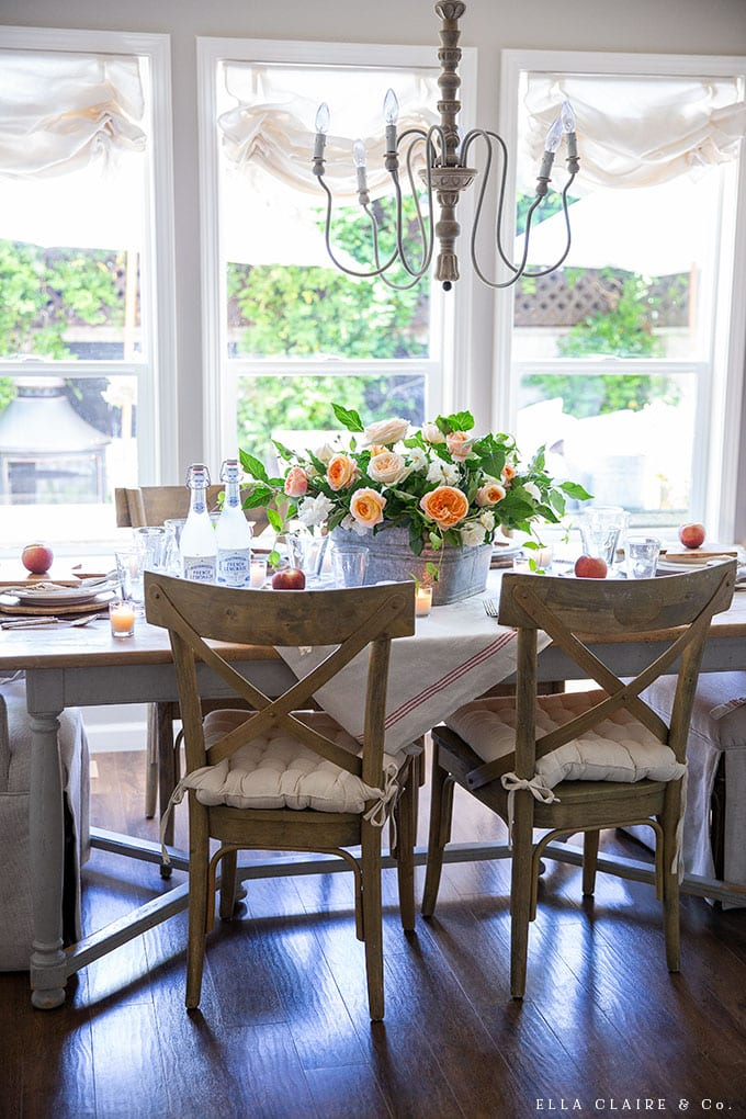 Garden roses and other yard clippings in an old wash basin, peaches, mini breadboards, and an old orchard blanket add simple vintage farmhouse charm to this DIY summer tablescape.