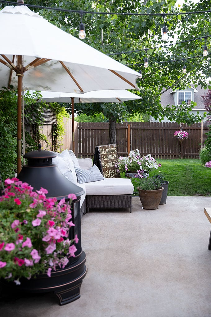 Warmth and coziness are added to this outdoor sitting area through pillows, a comfy cushion, umbrellas, and potted flowers and hanging baskets.