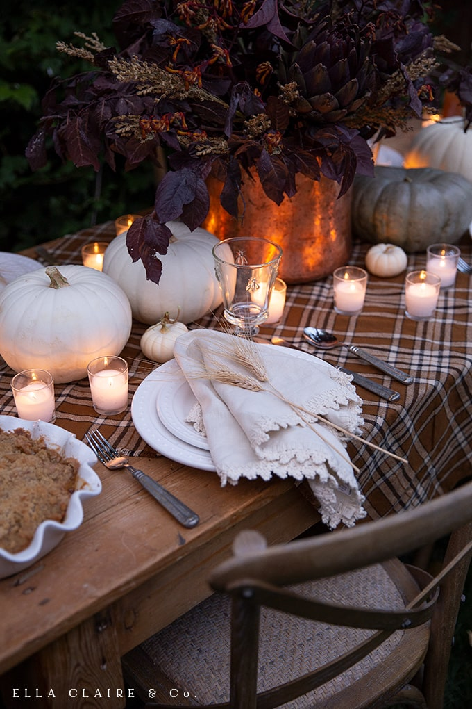 wheat on each place setting and scattered candlelight on a cozy fall table with plaid and pumpkins