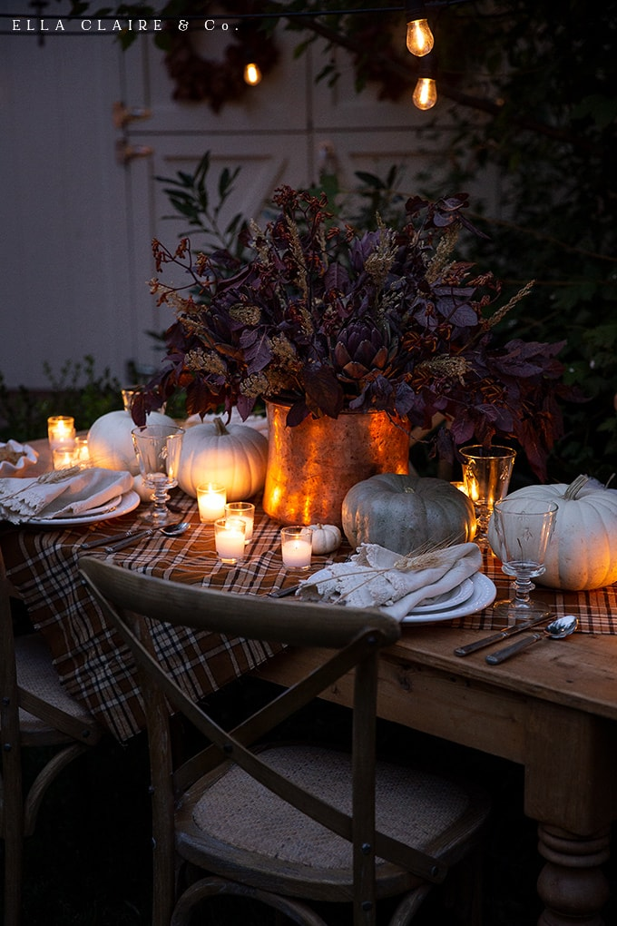 candlelight bouncing off of the copper and pumpkins on a beautifully set table in the evening is the sweetest way to celebrate fall