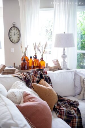 A cozy, rustic family room decorated for fall with touches of plaid, vintage amber glass, wood tones, and other antique elements,elements, enhanced with so much texture through blankets, throws and pillows.
