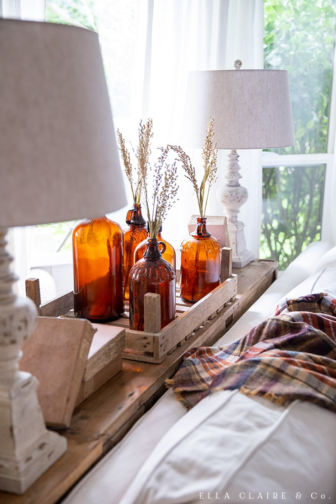 Amber glass is extra special near a window with the light shining through it. Paired with broomcorn, it is a quick and easy DIY centerpiece or decor idea.