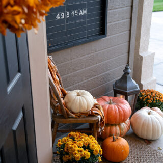 Fall porch with stacks of heirloom pumpkins, mums, and the warm glow of candles in a lantern