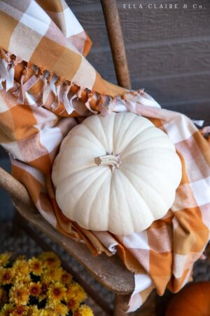 white pumpkins and nutmeg orange plaid on a cozy fall porch