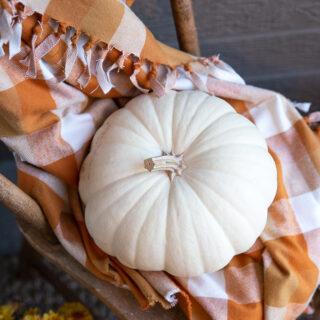 white pumpkins and nutmeg orange plaid on a cozy fall porch