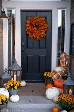 A welcoming and cozy Fall porch with stacks of heirloom pumpkins, mums, and the warm glow of candles in a lantern
