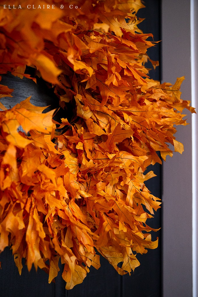 A DIY tutorial for this timeless and welcoming preserved leaf autumn wreath. Perfect with this fall porch decorated with lanterns, mums, pumpkins, and plaid with rustic vintage accents