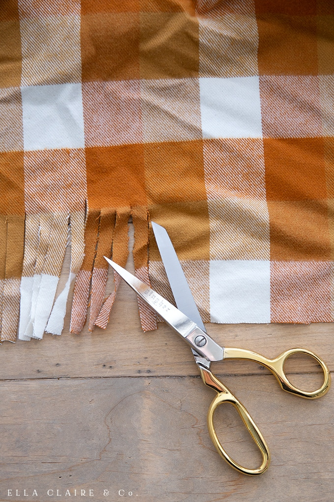 This easy DIY flannel blanket with a cute knotted fringe edge is perfect for layering on a cozy couch or chair or using as a tablecloth with your fall decor.