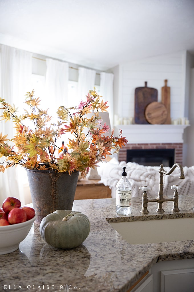 A cozy, rustic fall family room with antique breadboards as the focal point on the mantel.