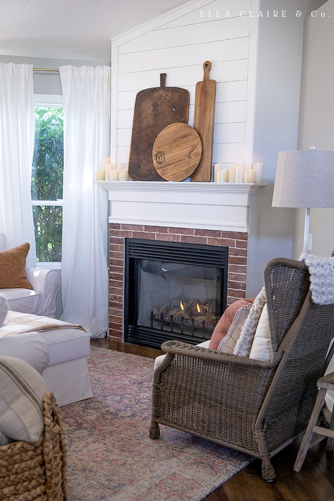 A cozy, rustic family room decorated for fall and set with the fireplace in for inviting people to get warm and stay awhile,