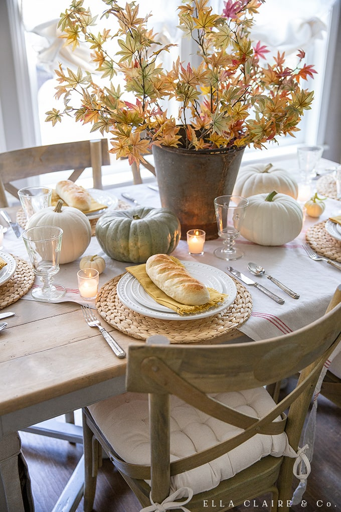 Fall leaves, mini bread loaves, and heirloom pumpkins are perfect additions to a fall tablescape