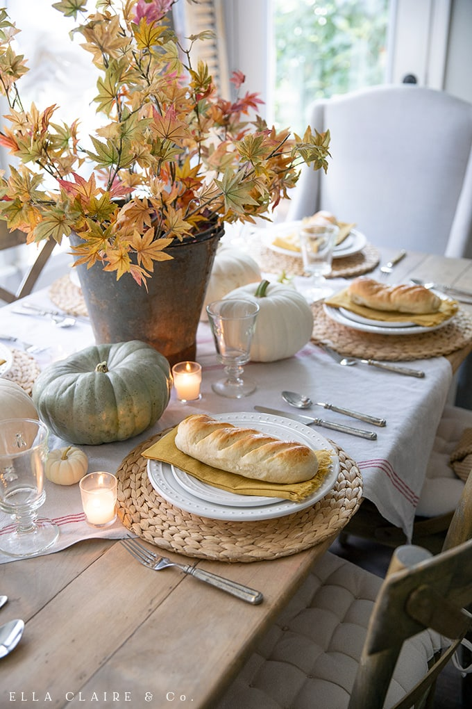 Mini French bread loaves and Fall leaves and heirloom pumpkins make this fall table cozy and inviting