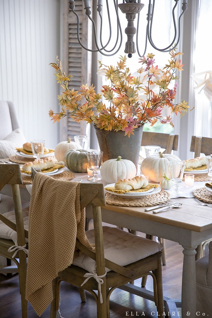 Thanksgiving would be cozy around this golden yellow rustic table with pumpkins and fall leaves