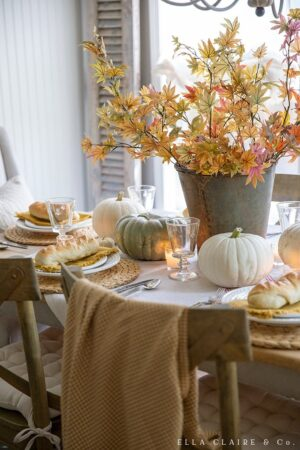 candlelight and pumpkins make this golden yellow table an inviting place to spend Thanksgiving.