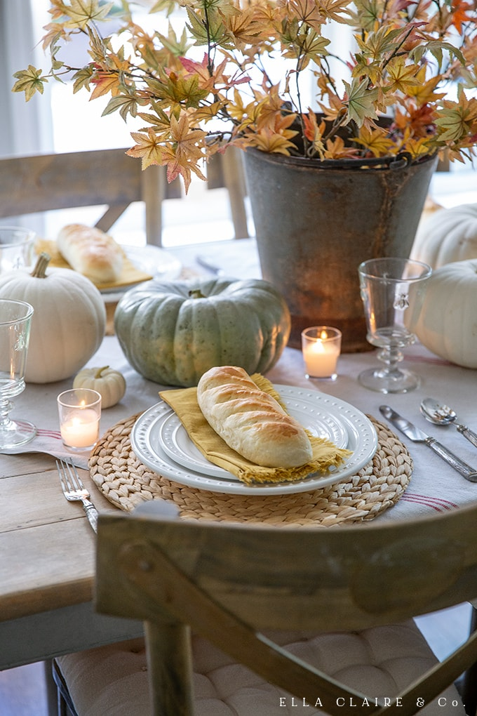 candlelight and mini bread loaves create a cozy ambiance for fall dinners or Thanksgiving entertaining