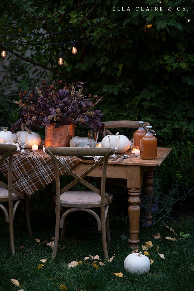 creating a cozy and inviting fall tablescape with rich warm colors, soft candlelight ambiance, pumpkins, wheat, and delicious food.