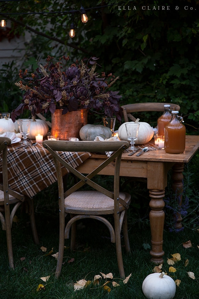 Simple ideas for creating a cozy and inviting outdoor (or indoor) fall tablescape with rich warm colors, soft candlelight ambiance, and delicious food.