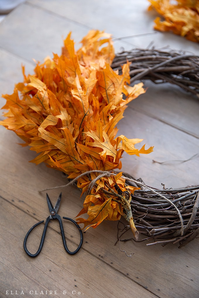 Attach the preserved fall leaves to the grapevine base to create a beautiful autumn wreath.