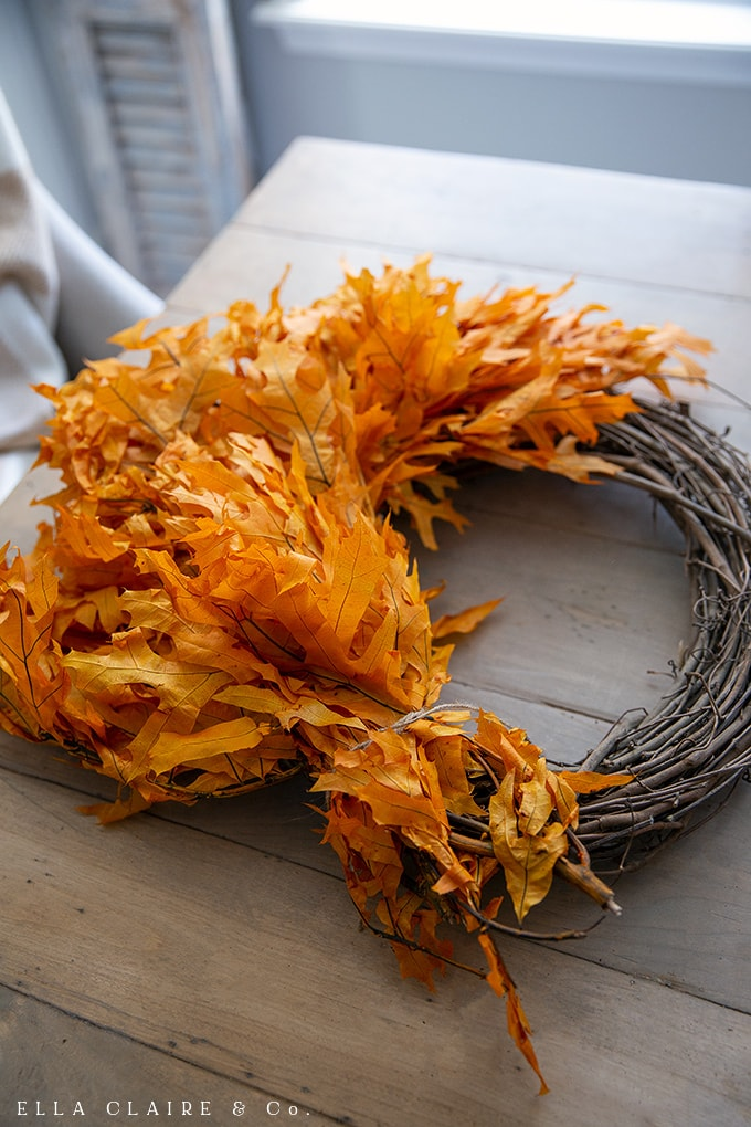 Continue to layer the preserved autumn leaves onto the grapevine wreath to create a very full fall wreath.