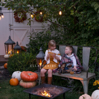 A cozy little fall family evening outdoors by the campfire sipping hot apple cider and roasting marshmallows while snuggled in plaid blankets under the glow of patio lights and candlelit lanterns.