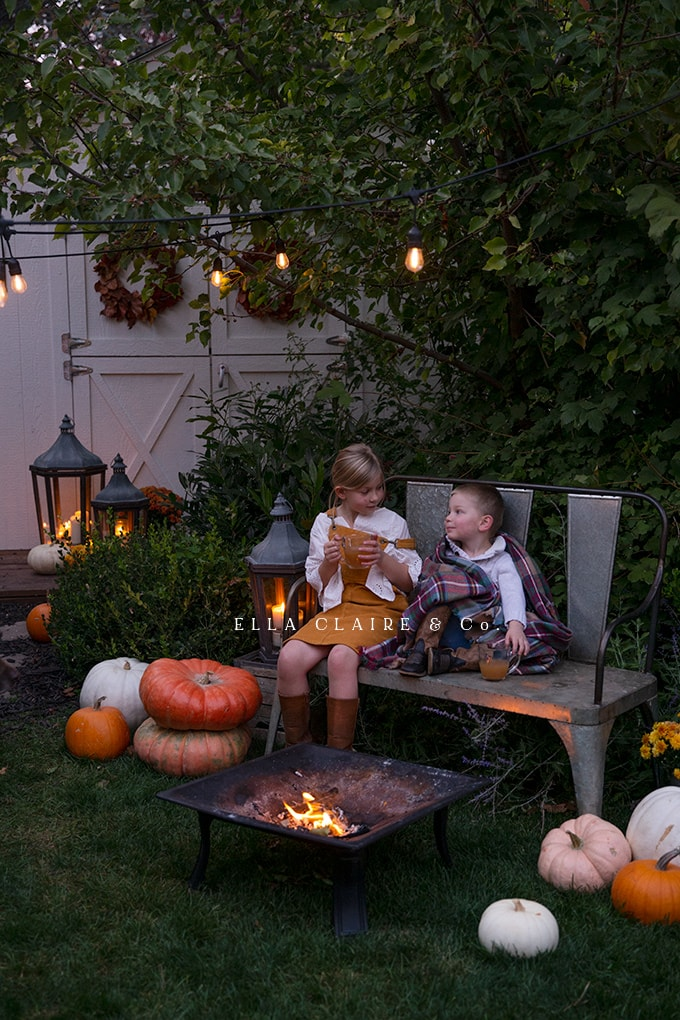 A Sweet Fall campfire for the littles with pumpkins and twinkle lights and yummy apple cider.