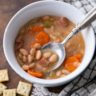 Easy and delicious slow cooker white bean and ham soup recipe takes only 10 minutes to throw together and the crockpot does all of the work! Serve with crusty bread or crackers and you have the perfect Fall or Winter Dinner.