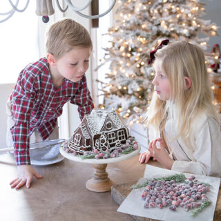 Children helping out in the kitchen making a homemade gingerbread cake with sugared cranberries, and powdered sugar on top.
