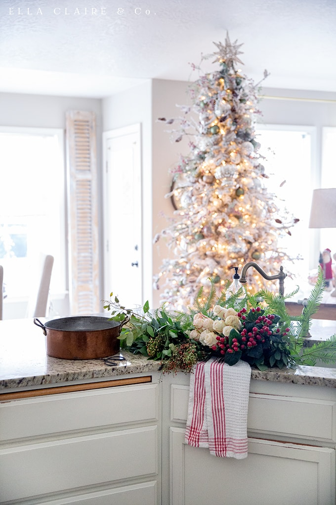 A very easy to throw together Christmas tablescape with traditional reds and greens, candlelight, neutral white dishes, and a view of the Christmas tree- a very cozy place to entertain holiday guests.