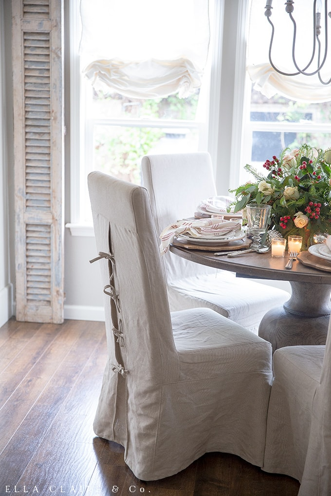 Parsons chairs at a wood table adorned with traditional Christmas colors and the soft glow of candlelight