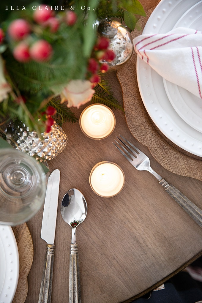 Cozy candlelight accents a Christmas tablescape.