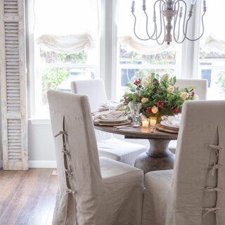 Parsons chairs at a wood table adorned with traditional Christmas colors and the soft glow of candlelight, an easy flower arrangement