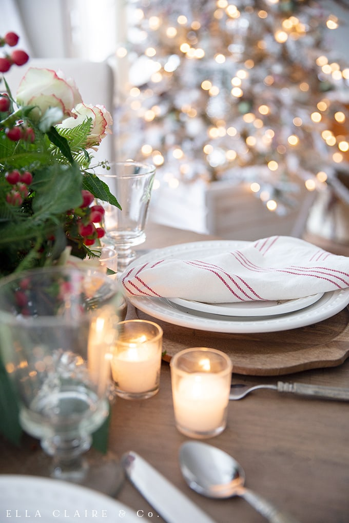 tablescape with traditional reds and greens under the glow of a Christmas tree