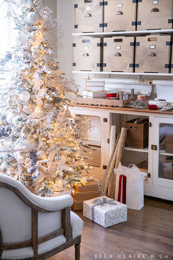flocked tree with blue and white accents next to a gift wrapping station.