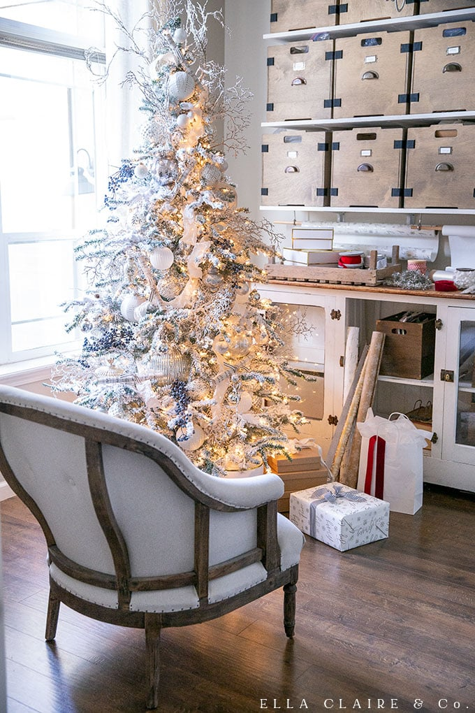 A gift wrapping station next to a beautiful flocked Christmas tree, decorated with whites, silvers, and clear ornaments for a French farmhouse style look.