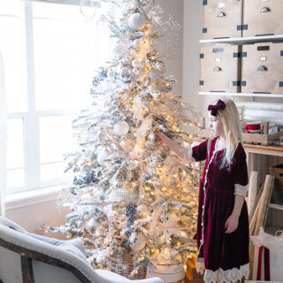 A sweet Christmas scene with little helpers decorating a beautiful flocked Christmas tree.