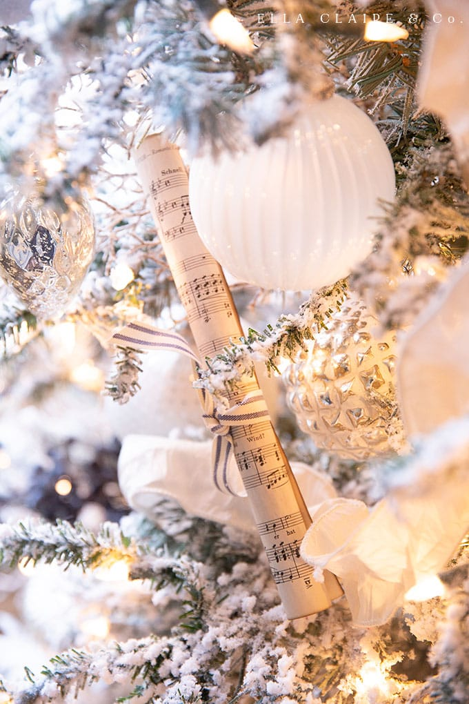 Details of a flocked Christmas tree decorated in shades of white and silver with Vintage sheet music accent.