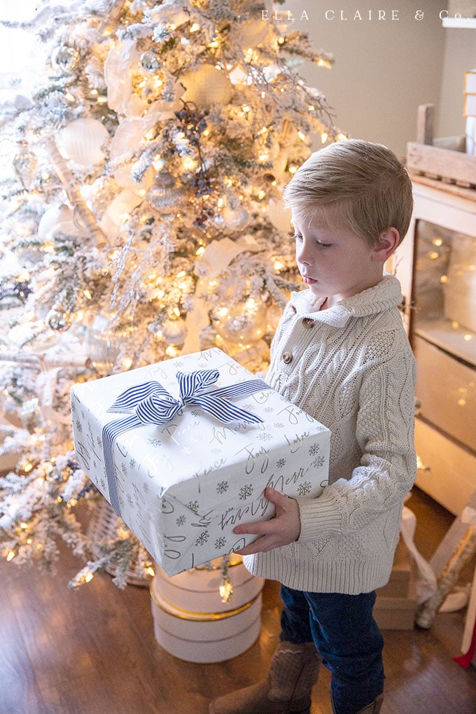Blue striped ribbon on Christmas wrapping paper ties in to the subtle blue accents of the Christmas tree.