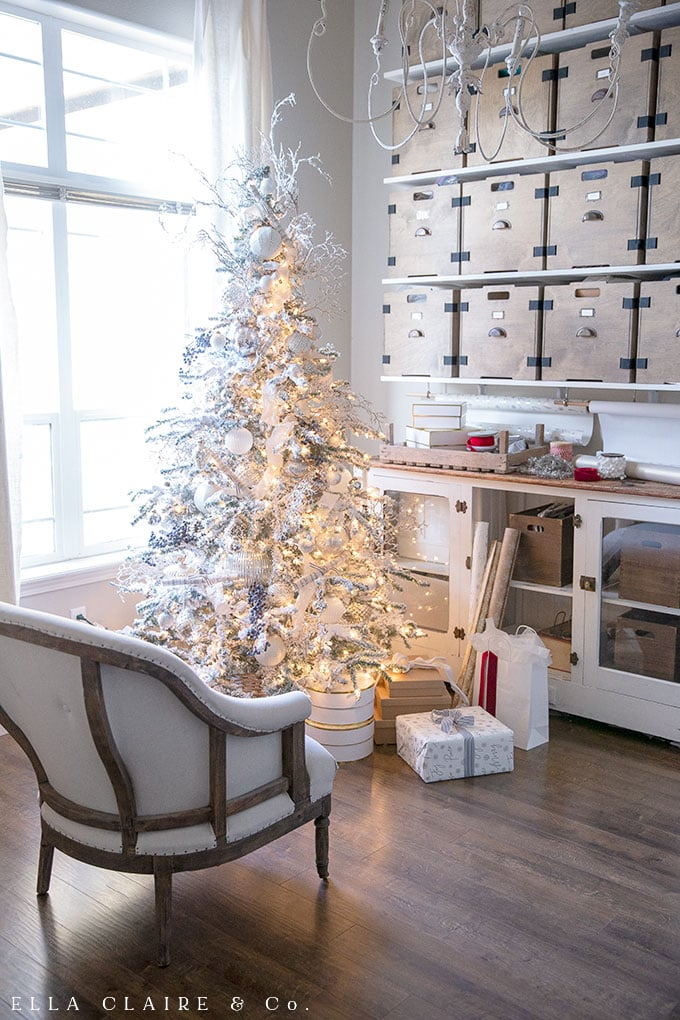 This flocked Christmas tree is effortlessly elegant, decorated in shades of white, clear, silver and a little bit of blue. In keeping with the traditional Christmas colors theme, little pops of red were added to the room with gift wrapping and ribbon.