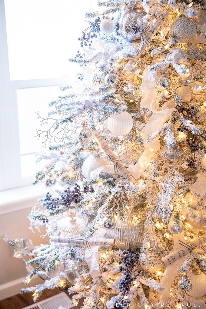 A flocked Christmas tree decorated with silver and white, with just a hint of s blue accent.